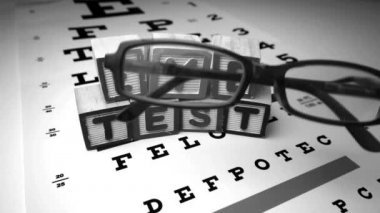 Glasses falling next to blocks spelling out eye test in black and white — Stock Video