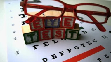 Glasses falling next to blocks spelling out eye test — Stock Video