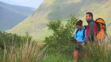 Active couple hiking together with map and pointing — Stock Video