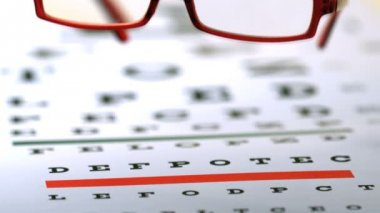 Red reading glasses falling on eye test — Stock Video