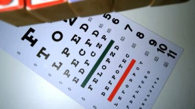 Colorful blocks spelling out sight falling on eye test — Stock Video