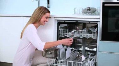 Blond kobieta umieścić jej naczynia w zmywarce i nie kciuki w kuchni — Wideo stockowe