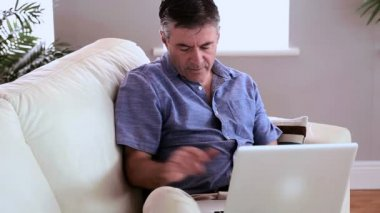 Mature man sitting on the couch using laptop and answering his phone — Stock Video