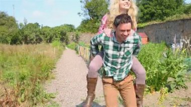 Handsome man giving piggy back to his girlfriend — Stock Video