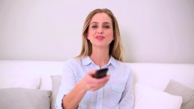 Blonde woman sitting on sofa watching television and changing channel — Stock Video