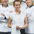 Waitress standing in front of team of chefs — Stock Photo