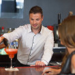 Handsome bartender serving cocktail to gorgeous woman — Stock Photo