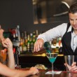Stock Photo: Handsome bartender serving cocktail to attractive woman