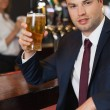 Stock Photo: Businessmholding pint of beer smiling at camera
