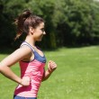 Fit womrunning in sunshine and smiling — Stock Photo #33435735