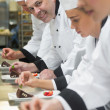 Stock Photo: Team of chefs in row garnishing dessert plates one smiling at camera
