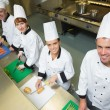Stock Photo: Four chefs preparing food at counter smiling at camea