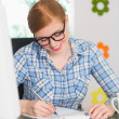 Happy redhead writing on notepad at her desk — Stock Photo