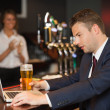 Businessman having a beer while working on his laptop — Foto de Stock