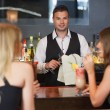 Handsome bartender working while gorgeous women talking — Stock Photo