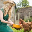 Young woman feeding her chickens — Stock Photo
