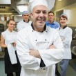 Head chef posing with his team behind him — Stock Photo #33436247