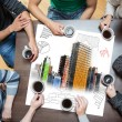 Overhead view of people sitting around table with painted city on sheet — Stock Photo