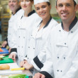 Four chefs standing in a row smiling at the camera — Stock Photo
