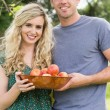 Young couple holding a bowl with apples — Stock Photo