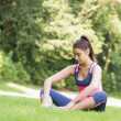 Young fit woman sitting on the ground — Stock Photo