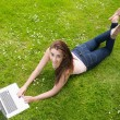 Happy young woman lying on a lawn using her laptop — Stock Photo