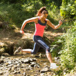 Sporty young woman leaping over a stream — Stock Photo #33436973
