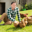 Young man feeding his chickens smiling at camera — Stock Photo