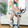 Handsome man training on exercise bike using tablet — Stock Photo