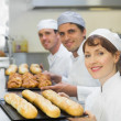 Three young bakers holding baking trays — Stock Photo #33437565