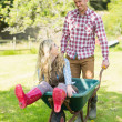 Happy man pushing his girlfriend in a wheelbarrow — Stock Photo