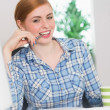 Happy redhead biting pen at her desk — Stok Fotoğraf #33437967