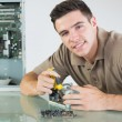 Stock Photo: Handsome cheerful computer engineer repairing hardware with pliers