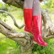 Woman wearing red rubber wellington boots sitting on a tree — Stock Photo