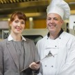 Mature head cook posing with the female manager  — Stock Photo