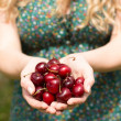 Close up of a blonde woman holding some cherries  — Stock Photo