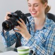 Happy photographer sitting at her desk looking at camera — Stock Photo
