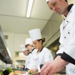 Four chefs preparing food at counter in a row — Stock Photo