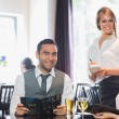 Business people and waitress smiling at camera — Stock Photo