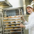 Pretty young female baker pushing a trolley — Stock Photo