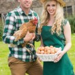Happy young couple holding chicken and basket of eggs — Stock Photo