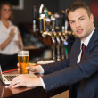Businessman having a pint while working on his laptop — Stock Photo