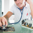 Handsome content computer engineer holding stethoscope — Stock Photo #33438815