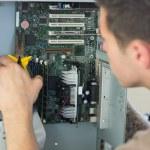 Computer engineer repairing open computer with pliers — Stock Photo #33438923