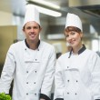 Two young chefs posing in a kitchen — Stock Photo