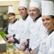 Four chefs working at serving trays — Stock Photo