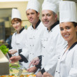 Four chefs working at serving trays — Stock Photo #33439091