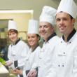 Four chefs working in a kitchen standing in a row — Stock Photo