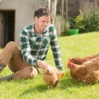 Young man feeding his chickens — Stock Photo #33439221