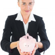 Cute businesswoman holding a piggy bank — Stock Photo